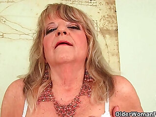 Grandmother with large breasts pushes huge black dildo inside